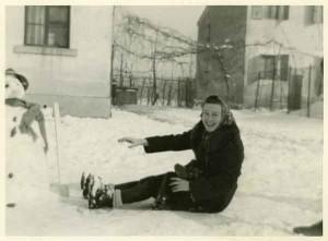 la maestra Giulia ride sulla neve vicino al pupazzo appena realizzato dai suoi alunni