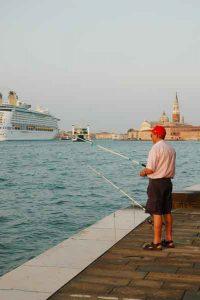 un pescatore sulla riva e una nave sullo sfondo